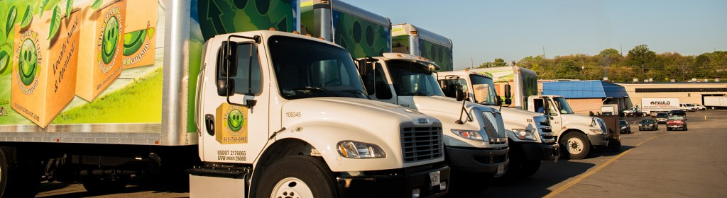 moving trucks lined up outside of The Green Truck Moving & Storage Company